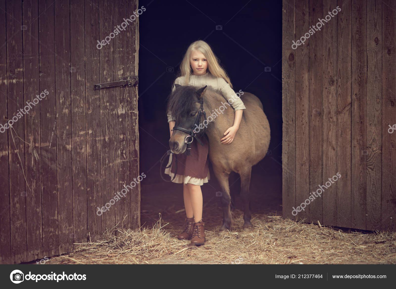 Girl Hugging Pony Looking Camera While Standing Doors Barn