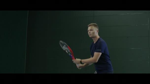 Mladý muž, hrát tenis a kuličky s raketou na vnitřní dvůr