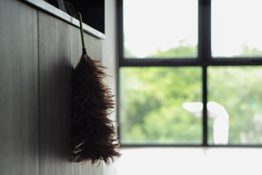Silhouette of feather broom hanging from the wooden counter with blurred background