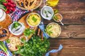 Wiesn-Bier, Brezeln und verschiedene bayerische Spezialitäten auf Holzboden