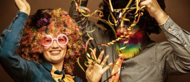 Happy man and woman wearing color wigs with party items