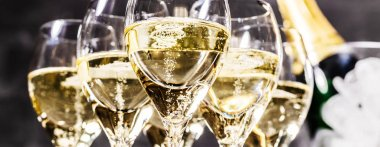 Champagne bottle and glasses on dark background, close up