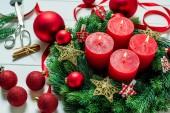 Fotografie Adventskranz mit vier roten Kerzen und Kugeln