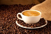 Fotografie cup of coffee and  cake on coffee beans.