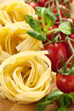 Tagliatelle pasta with fresh basil and tomatoes on rustic table