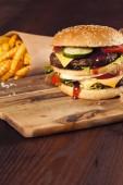 Rychlé občerstvení hamburger a hranolky na dřevěné pozadí