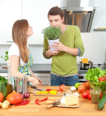 Happy sporty couple is preparing healthy food on light kitchen. Healthy food concept