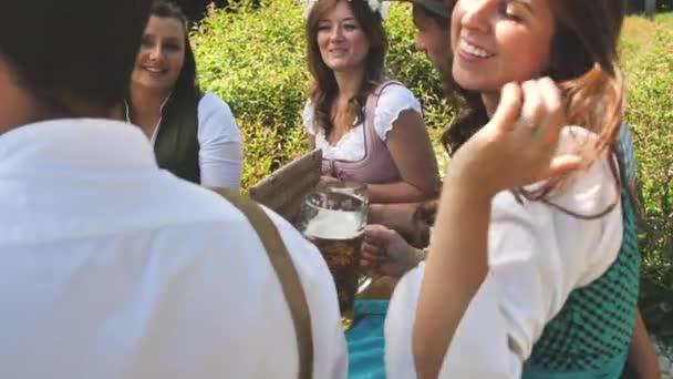 Gruppe fröhlicher junger Freunde trinkt Bier und isst Brezeln beim Picknick an einem sonnigen Sommertag