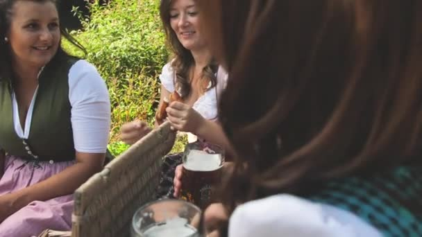 group of happy young friends drinking beer and eating pretzels during picnic at sunny summer day