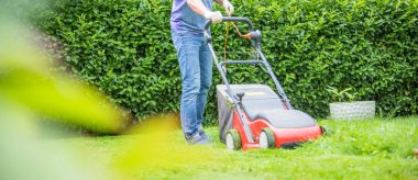 Summer and spring season. Man mowing lawn in the garden during sunny