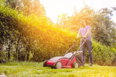 Summer and spring season. Man mowing lawn in the garden during sunny day