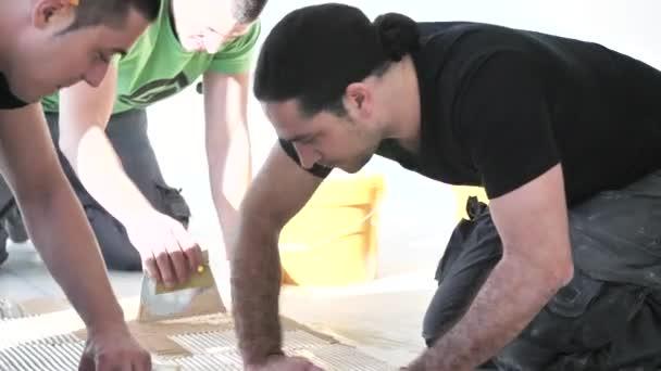 workers installing oak parquet floor during home improvement