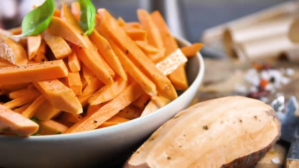 Nahaufnahme der Schüssel mit leckeren Süßkartoffeln, Basilikumblättern, Löffel und Knoblauch auf dem Tisch