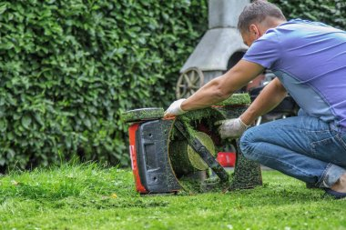 man mowing lawn in the garden during sunny day