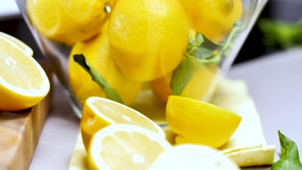 Nahaufnahme von frischen saftigen ganzen und halbierten Zitronen, grünen Blättern und Glasschale auf dem Tisch