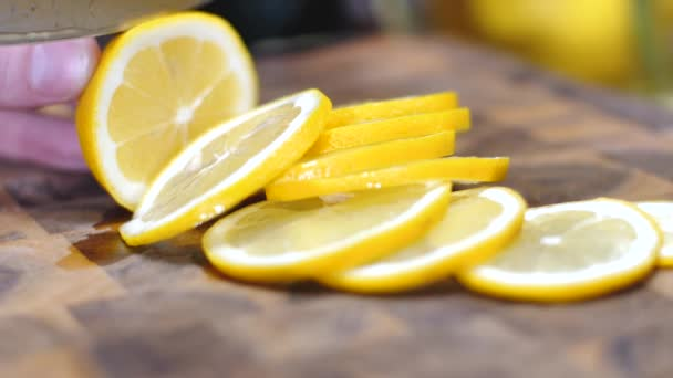 close-up partial view of person holding knife and slicing fresh ripe lemon on cutting board