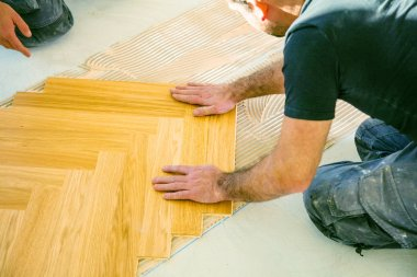 cropped shot of workers installing oak parquet floor during home improvement