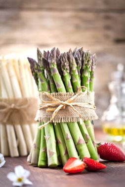close-up view of bunches of fresh green and white asparagus and ripe strawberries on wooden table, selective focus