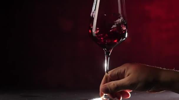 abgeschnittene Aufnahme einer Person, die Rotwein im Glas auf dunkelrotem Hintergrund schüttelt