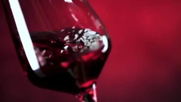 podrobný pohled na červené víno třesoucí se ve skle na tmavě červeném pozadí