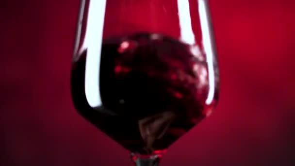 Nahaufnahme von Rotwein, der im Glas vor dunkelrotem Hintergrund zittert