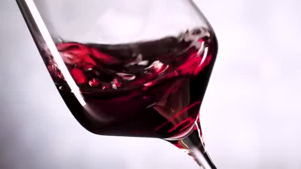 close-up view of red wine shaking in glass on grey background