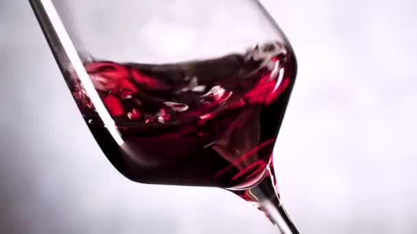 podrobný pohled na červené víno třesoucí se ve skle na šedém pozadí