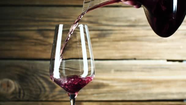 Nahaufnahme einer Person, die Rotwein ins Glas gießt