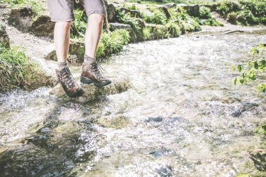 low section of male hiker stepping on stones at rapid river