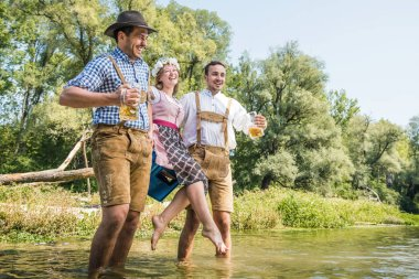 happy young friends in Bavarian costumes holding glasses of beer and walking outdoor, oktoberfest concept