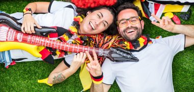 Enthusiastic German sport soccer fans celebrating victory, lying on grass and playing guitar