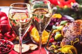jídelní stůl s sklenicemi šampaňského, lahodné jídlo a slavnostní dekorace, vánoční koncept