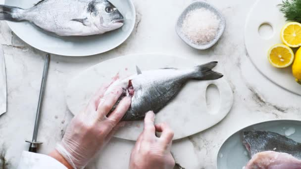 cropped shot of chef wearing gloves and cooking delicious fish