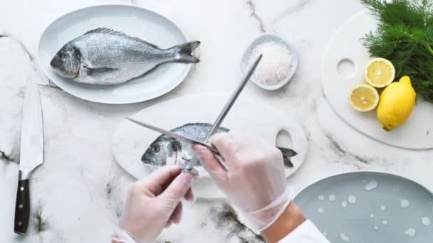 levágott lövés szakács visel kesztyű és főzés finom hal