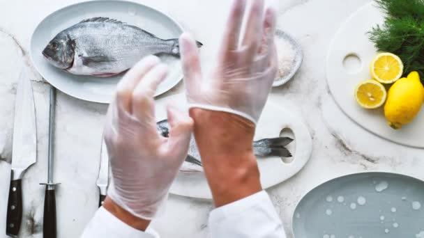 Schnappschuss von Koch mit Handschuhen und köstlichem Fisch