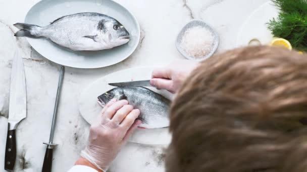 ostříhaný záběr kuchaře v rukavicích a vaření lahodné ryby