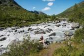 tramp sedí poblíž horské řeky na hřebeni Besseggen v národním parku Jotunheimen, Norsko