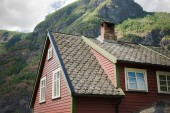 Photo low angle view of beautiful wooden house in Flam village and majestic mountains, Aurlandsfjord (Aurlandsfjorden), Norway