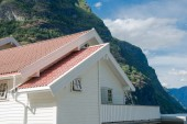 Photo white wooden house with red roof near beautiful mountains at Aurlandsfjord, Flam (Aurlandsfjorden), Norway