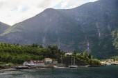 Fotografia edifici e yacht ormeggiati sul lago calmo vicino a bellissime montagne in Norvegia