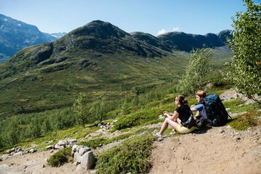 couple of hikers resting on Besseggen ridge in Jotunheimen National Park, Norway