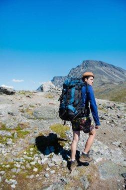 Traveler with big backpack hiking on Besseggen ridge in Jotunheimen National Park, Norway stock vector