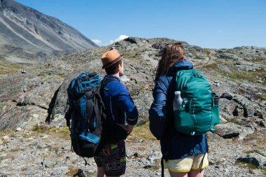 Hikers with backpacks on Besseggen ridge in Jotunheimen National Park, Norway stock vector
