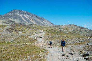 couple of hikers walking on path on Besseggen ridge in Jotunheimen National Park, Norway