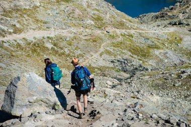 Couple on travelers hiking on Besseggen ridge in Jotunheimen National Park, Norway stock vector