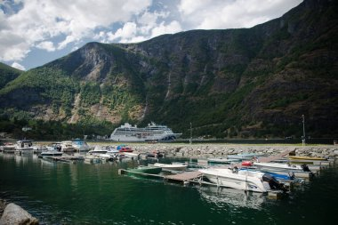 AURLANDSFJORD, FLAM, NORWAY - 27 JULY, 2018: boats moored in harbour and beautiful mountains at Aurlandsfjord, Flam (Aurlandsfjorden), Norway