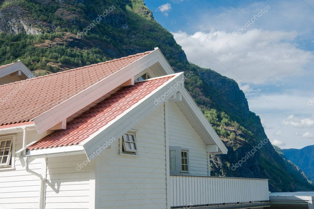 white wooden house with red roof near beautiful mountains at Aurlandsfjord, Flam (Aurlandsfjorden), Norway