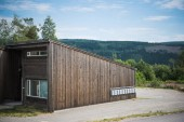Fotografie wooden building with green mountain on background, Trysil, Norways largest ski resort