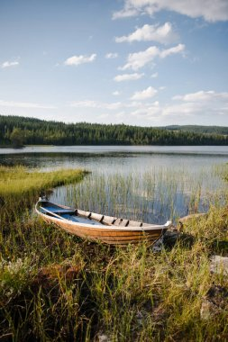wooden boat near lake in front of forest in Trysil, Norway's largest ski resort