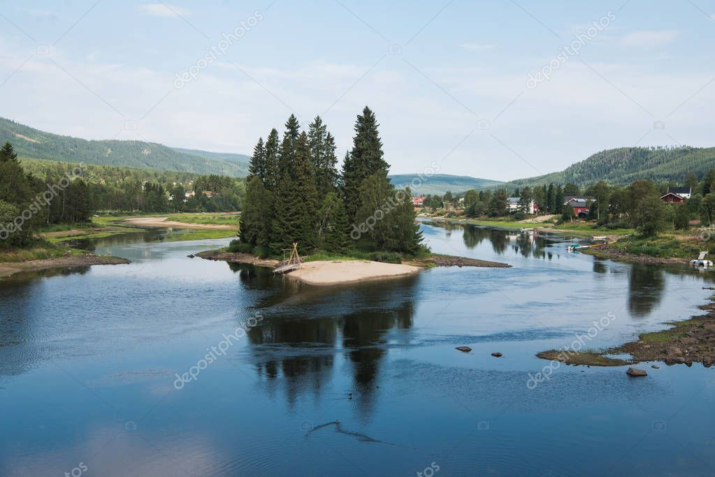 small island with fir trees on river, Trysil, Norway's largest ski resort
